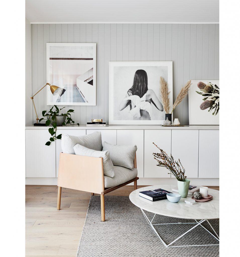 interiér v škandinávskom štýle v bielych tónoch na drevenom obklade, oválnom stolíku a kresle