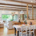 jedálenský stôl s ľanovým obrusom a drevenými stoličkami s výhľadom do obývačky a záhrady
