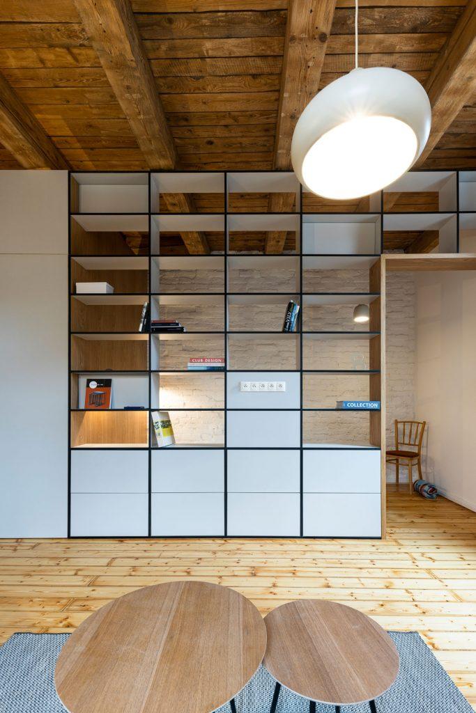 interiér s knižnicou, ktorá oddeľuje priestor na dve zóny