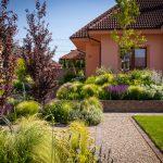 rodinný dom so záhradou vo svahu, v ktorej sú rastliny nasadené vo vyvýšených záhonoch