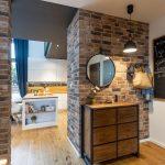 chodba mezonetového bytu zariadená v industriálnom štýle s tehlovou stenou, na ktorej visí zrkadlo s dreveno-kovovou skrinkou