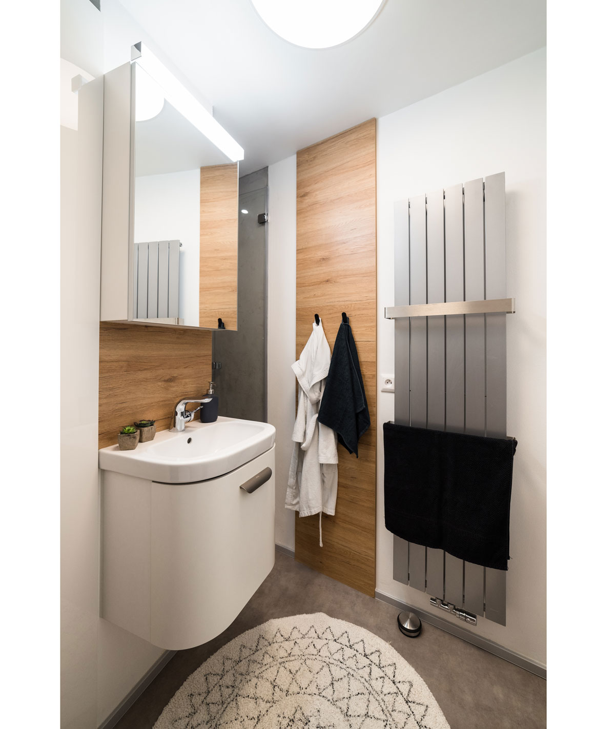 kúpeľňa v garsónke so závesným umývadlom, radiátorom na osušky a drevenými prvkami
