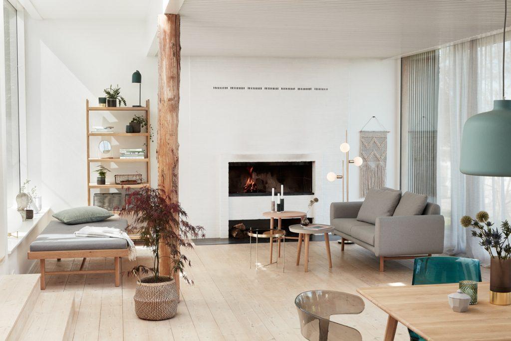 interiér v škandinávskom štýle v prírodných tónoch, so svetlou drevenou podlahou, dreveným regálom a stolíkmi a sedením v zemitých farbách