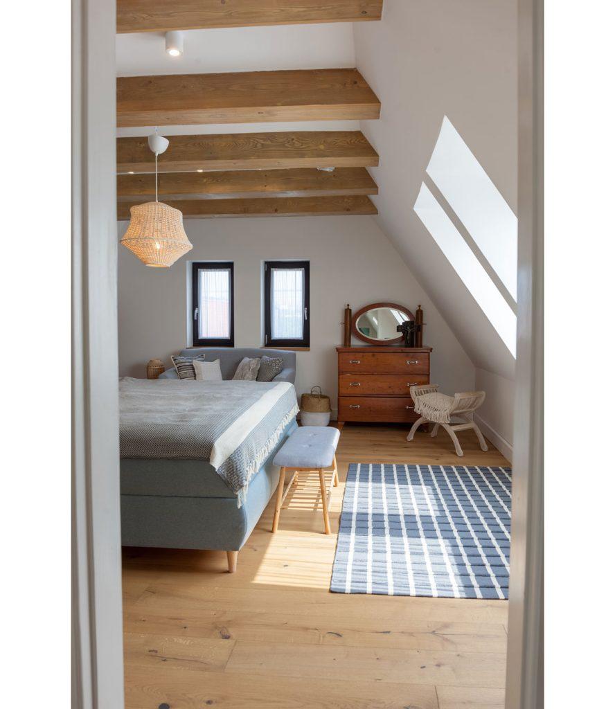 Spálňa vo vidieckej chalupe v podkroví so zalomenou strechou a drevenými trámami