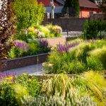 vyvýšené murované záhony v modernej záhrade s okrasnými trávami, trvalkami a krami