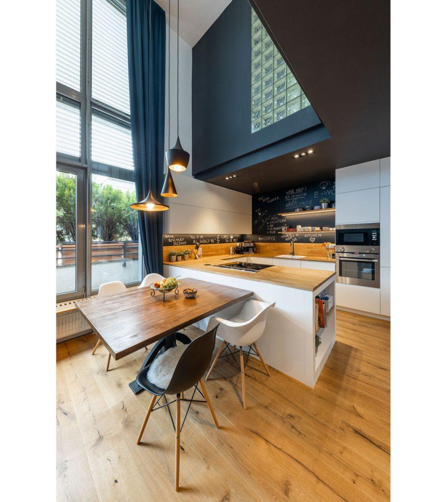 kuchyňa v industriálnom štýle s drevenou kuchynskou zostavou, dreveným stolom a dizajnovými plastovými stoličkami, čiernymi závesmi a čiernou tabuľovou stenou