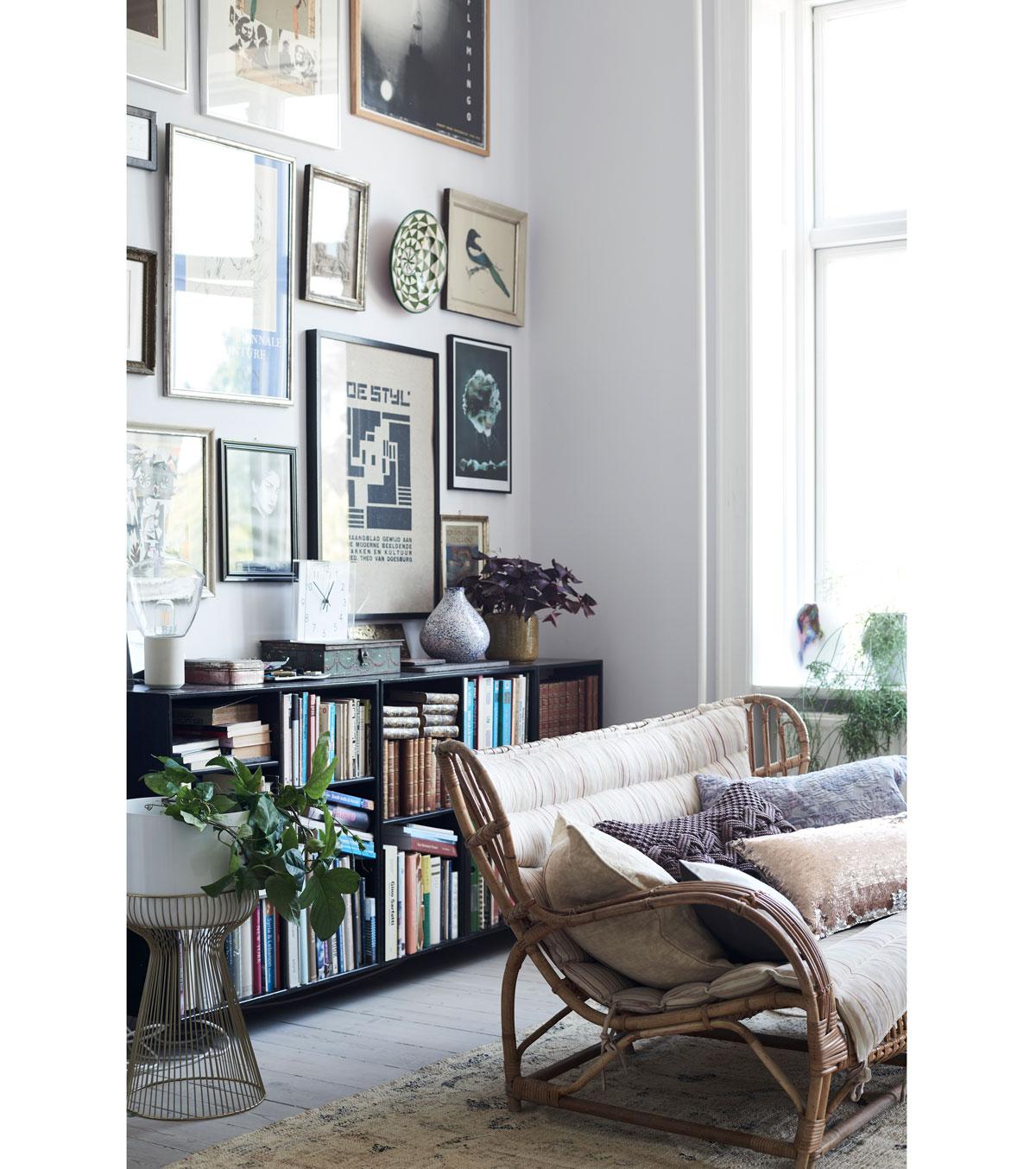 retro obývačka s čiernou knižnicou, obrazmi a kreslom z prírodného materiálu