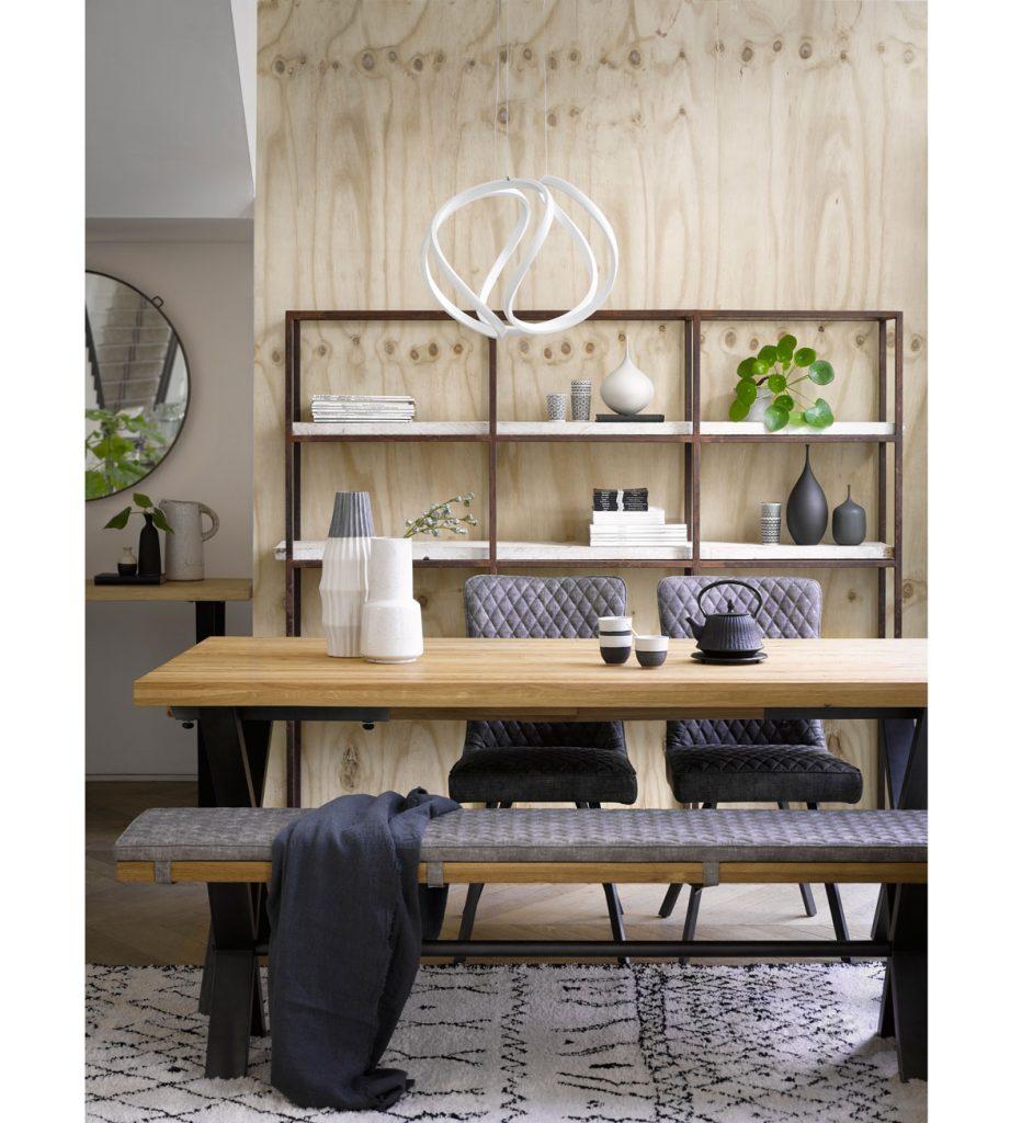jedáleň v minimalistickom japandi štýle s drevenou lavicou a stolom, modrými čalúnenými stoličkami, kovovým otvoreným regálom a dreveným obkladom na stene