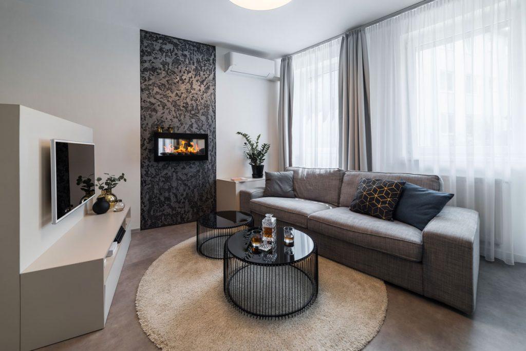 obývačka v garsónke v pánskom duchu, v modernom minimalistickom štýle s biokrbom, okrúhlymi stolíkmi, sedačkou a televíznou stenou