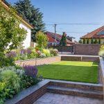záhrada vo svahu s vyvýšenými záhonmi, v ktorých sú pestrofarebné trvalky, okrasné trávy a stromy