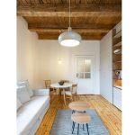 obývačka s jedálenským stolom v jednoizbovom byte, s oválnymi stolíkmi, šedým kobercom, sedačkou v prírodnom štýle, drevenou podlahou a odhaleným trámovým stropom