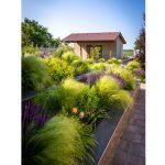 rodinný dom so záhradou vo svahu s vyvýšenými záhonmi, v ktorých sú kvitnúce trvalky a okrasné trávy