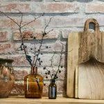 polička s drevenými lopármi, hlineným džbánom a sklenenými vázami
