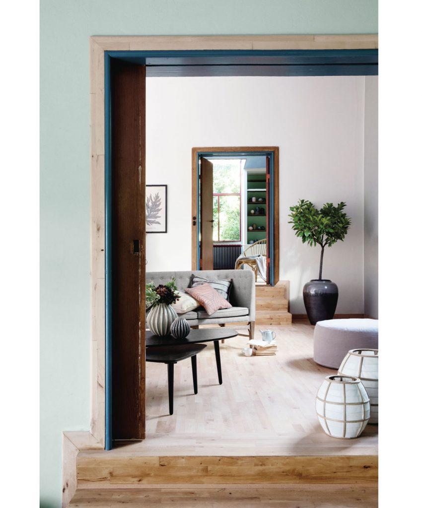 jednoduchá obývačka v japandi štýle so sivou pohovkou, čiernymi stolíkmi, taburetkou a so stromčekom v rozmernom keramickom kvetináči