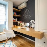 drevený pracovný stôl s plastovou dizajnovou stoličkou a čiernou tabuľovou stenou v dievčenskej izbe zariadenej v industriálnom duchu