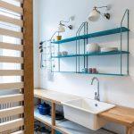 kuchyňa so závesnými otvorenými policami, pracovným stolom a zabudovaným umývadlom