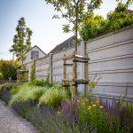 záhon s bylinkami, kvitnúcimi trvalkami a okrasnými trávami situovaný pri plote rodinného domu