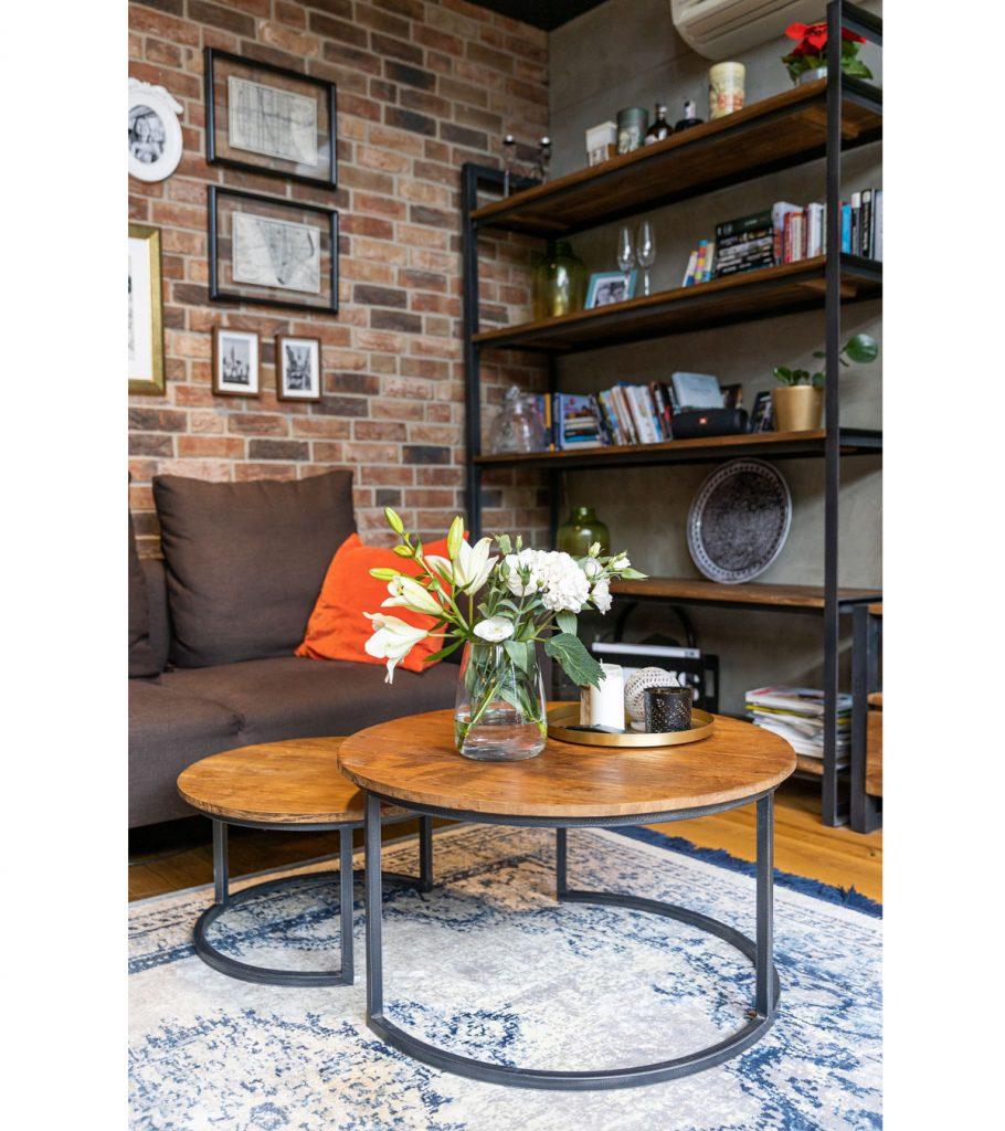 industriálny interiér s hnedou sedačkou, dreveným okrúhlym stolíkom na kovovej konštrukcii, s dreveno-kovovým regálom a tehlovou stenou