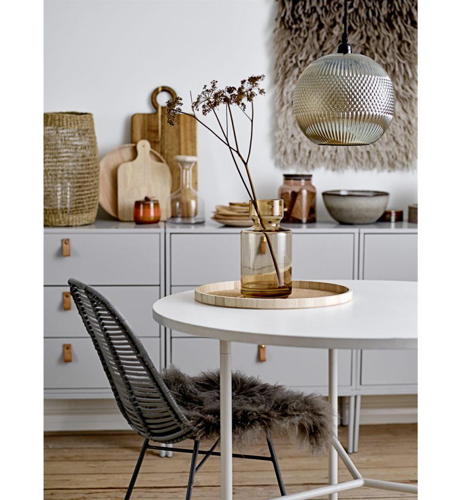 interiér v severskom štýle s oválnym bielym stolom a bielou skrinkou, pleteným kreslom s kožušinou a dekoráciami zo skla, dreva a kovu