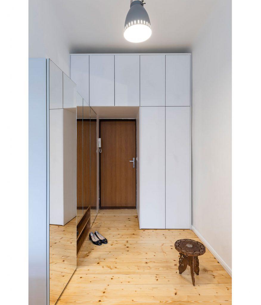 chodba v jednoizbovom byte s drevenou podlahou, úložnými priestormi a zrkadlovou stenou
