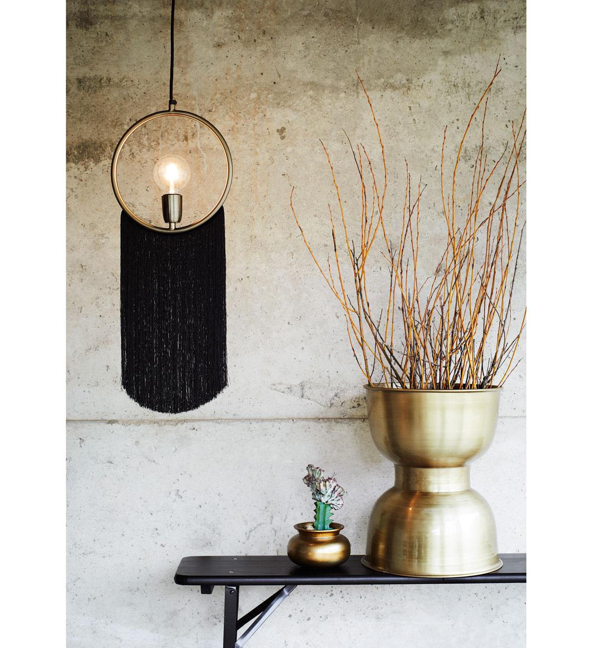 okrúhle svietidlo s dlhými strapcami a polička s metalickými vázami