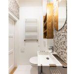 kúpeľňa v jednoizbovom byte s obkladom v imitácii terazzo, umývadlom, wc a drevenou policou