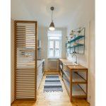 kuchyňa v jednoizbovom byte, zariadená pôvodnou kuchynskou linkou a pracovným dreveným stolom s policami, v ktorom je zabudované umývadlo, nad stolom sú zavesené otvorené police na kovových držiakoch