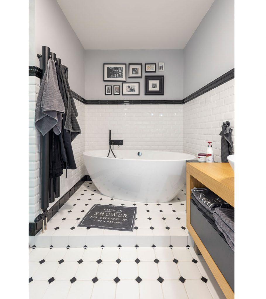 industriálne ladená kúpeľňa so samostatne stojacou vaňou, drevenou skrinkou, bielym obkladom a bielo-čiernou podlahou, s obrazmi na stenách