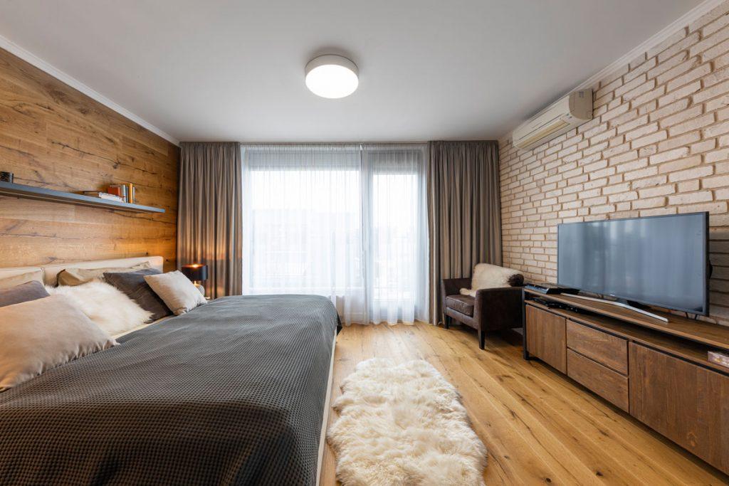 industriálne ladená spálňa v odtieňoch čiernej, béžovej a bielej, s tehlovou stenou, drevenou podlahou, kožušinou na zemi, drevenou skrinkou s televíziou, kresielkom a manželskou posteľou