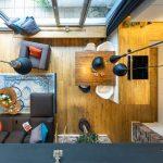 pohľad zhora na obývačku prepojenú s kuchyňou nachádzajúce sa v mezonetovom byte v industriálnom štýle
