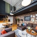 kuchyňa s obývačkou v mezonetovom byte v industriálnom štýle, so sivohnedou pohovkou, nábytkom v kombinácii dreva a kovu, s tehlovou stenou a čiernou tabuľovou stenou zasahujúcou do poschodia