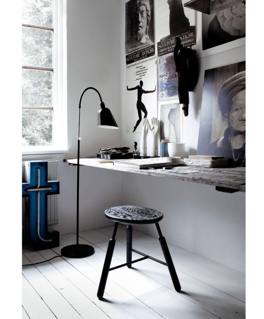 pracovný kút pre muža s drevenou surovou doskou pripevnenou o stenu, jednoduchou trojnožkovou stoličkou a s vysokou lampou