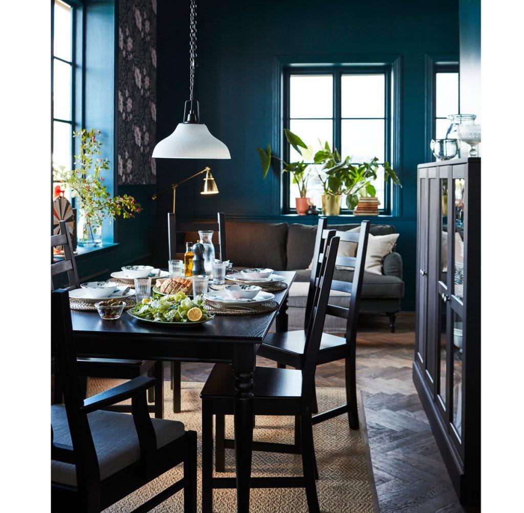 interiér v škandinávskom štýle s tmavým jedálenským stolom a stoličkami, skrinkou na kuchynské riady, sivou sedačkou a tmavomodrými stenami