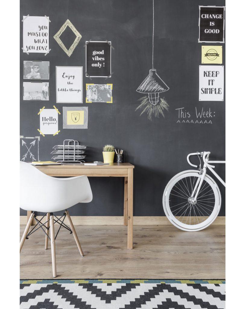 pracovný kút v detskej izbe s tabuľovou stenou, jednoduchým dreveným stolom a bielou stoličkou