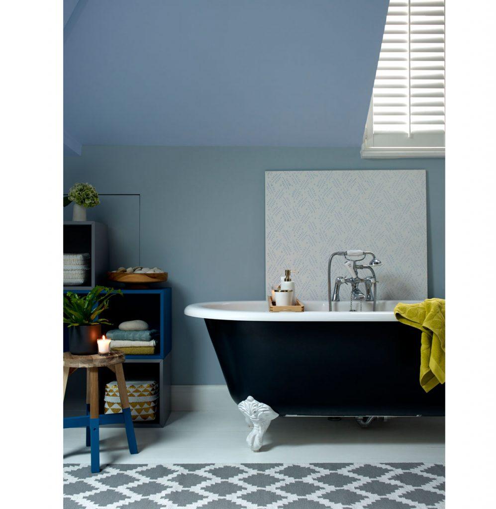 kúpeľňa v modrých odtieňoch s výraznou čiernou vaňou na bielych zdobených nožičkách, s retro sprchou, štvorcovými skrinkami a dreveným stolíkom