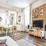 zrekonštruovaný starý byt so smrekovými podlahami, jedálenským kútom, drevenou rebrinou s policami a zavesenou TV a skrinkami predelenou bielou kuchyňou