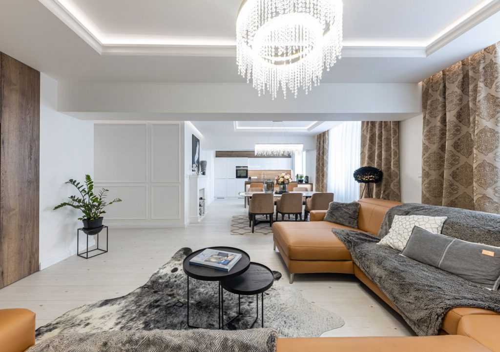 pohľad do otvoreného glamour interiéru s koženou hnedou sedačkou, krištáľovým lustrom, z obývačky sa priestor delí na jedáleň a kuchyňu