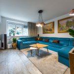obývačka s veľkou zamatovou sedačkou v modrej farbe, dreveným retro stolíkom, lesklou tv stenou, atmosférovým osvetlením, impresionistickými obrazmi a podlahou s imitáciou kameňa