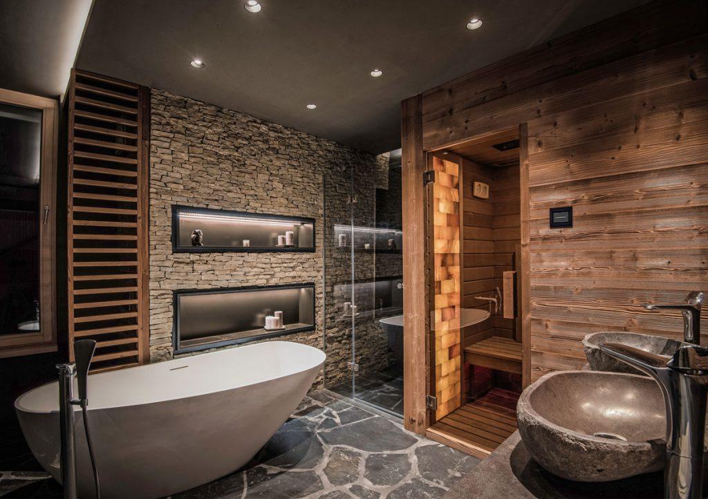 kúpeľňa vo wellness štýle s kamenným obkladom a dlažbou, dreveným obložením, samostatne stojacou vaňou, kamenným umývadlom a saunou