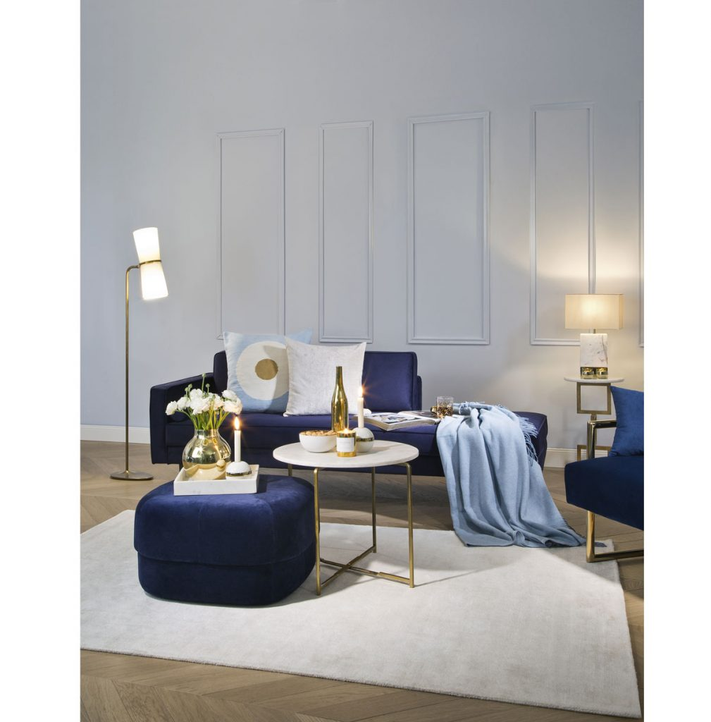 obývačka v art déco štýle, s modrou pohovkou a okrúhlym bielym stolíkom na zlatých nožičkách