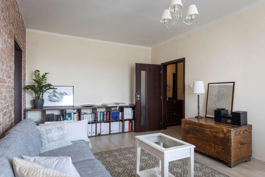 paneláková obývačka vo francúzskom rustikálnom štýle so sivou sedačkou, bielym vidieckym stolíkom, knižnicou z tmavého dreva a komodou
