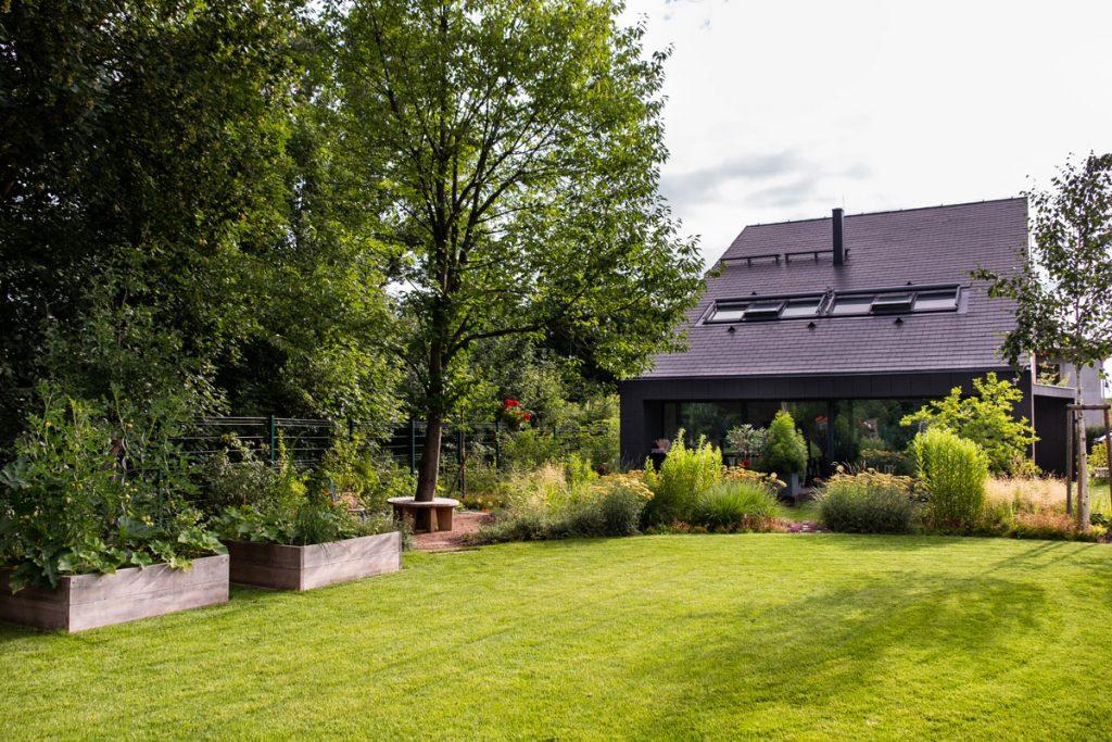 rodinný dom so záhradou s trvalkovými záhonmi, lavičkou okolo stromu a vyvýšenými záhonmi