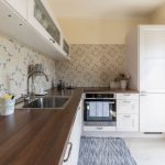 kuchyňa vo francúzskom vidieckom štýle s bielou kuchynskou linkou, behúňom a vzorovaným obkladom na zástene