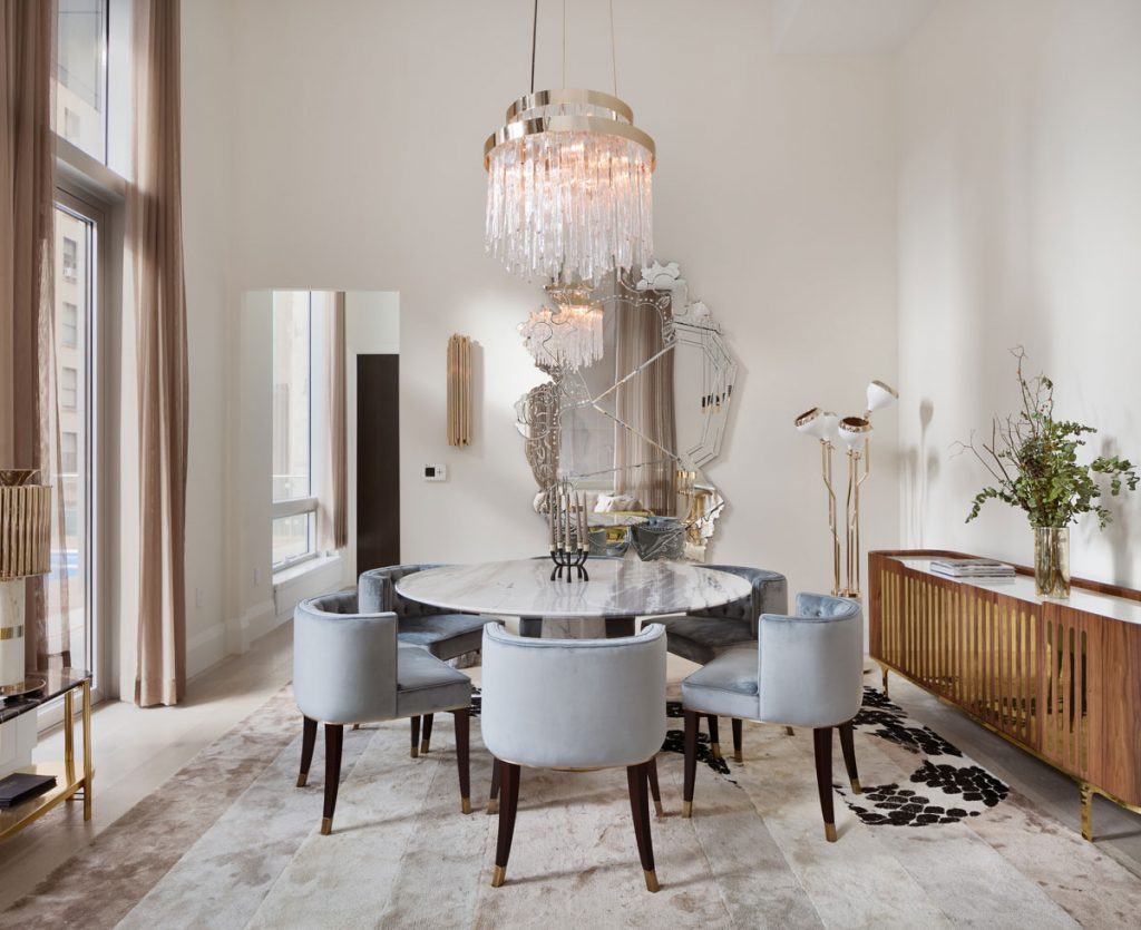 jedáleň v art déco, s okrúhlym stolom, zamatovými stoličkami, drevenou komodou, zlatou stojacou lampou, mohutným nepravidelným zrkadlom a krištáľovým lustrom