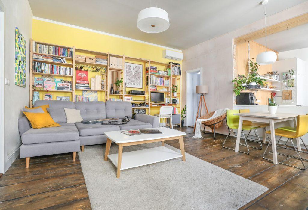 otvorený priestor obývačky s jedálenským stolom, so sivou pohovkou a drevenou policovou zostavou pri žltej stene