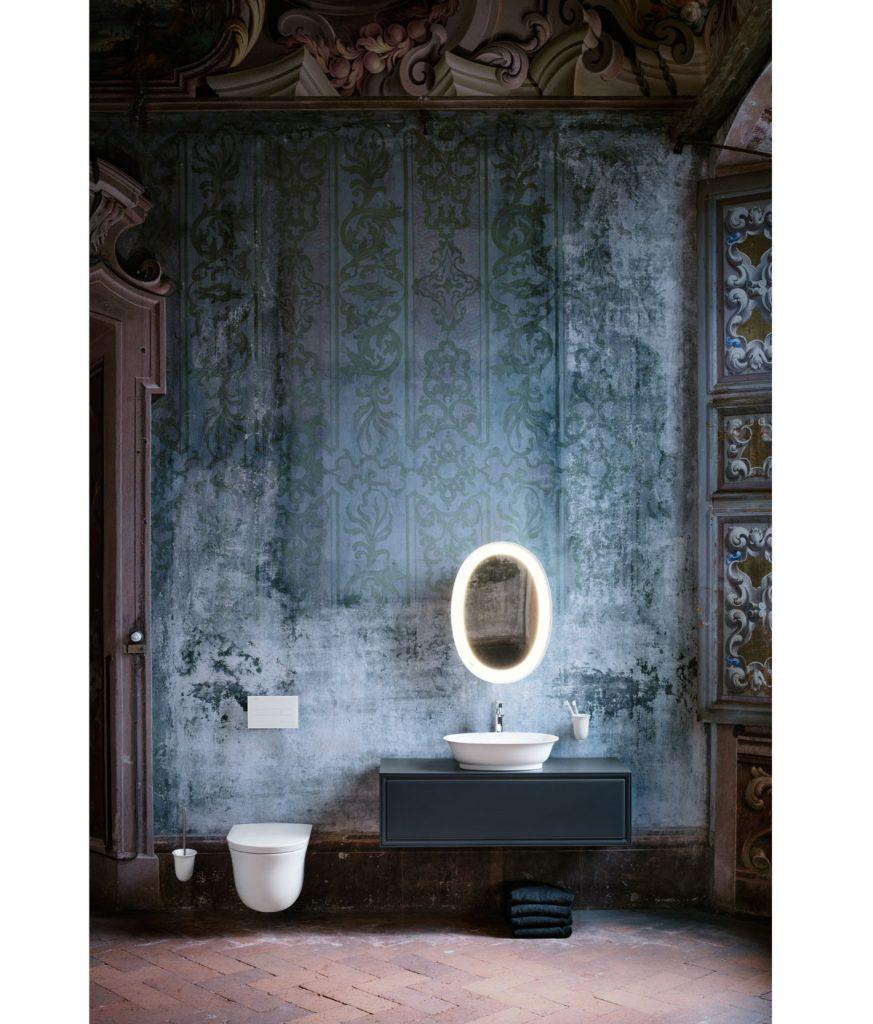 kúpeľňa spojená s WC, so vzorovanou modrou maľovkou vo vzhľade starej oškrabanej farby, s oválnym podsvieteným zrkadlom a umývadlom stojacim na modrej skrinke