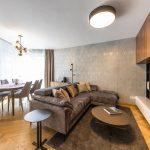 obývačka s jedálňou v glamour retro štýle, s drevenými podlahami, art déco tapetami, dizajnovými svietidlami, modernou sedačkou a minimalistickou retro tv stenou