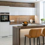 minimalistická kuchyňa v bielo-hnedom prevedení s barovými koženými stoličkami
