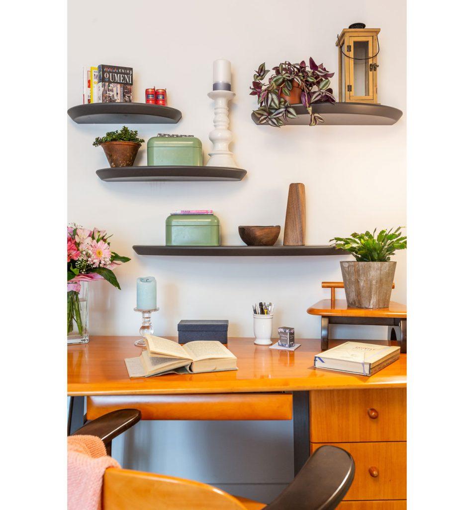 pracovný kútik ako súčasť spálne, zariadený retro lakovaným masívnym stolom a poličkami, na ktorých sú dekorácie a izbové rastliny