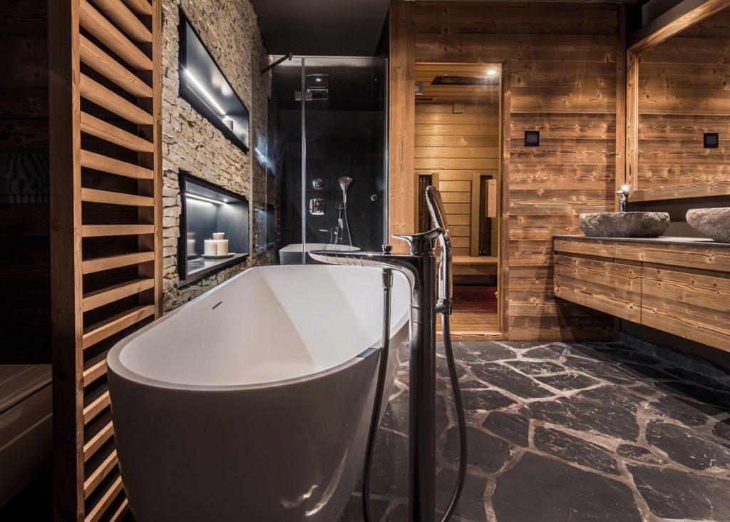 wellness kúpeľňa so samostatne stojacou vaňou, kamennou podlahou a kamenným obkladom na stene, saunou, dreveným obkladom a intímnym osvetlením
